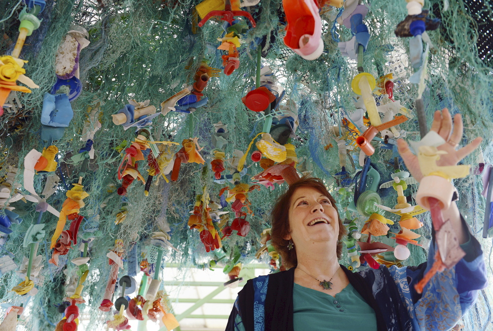 """Angela Haseltine Pozzi stands under her work """"Ocean Gyre,"""" which is part of the """"Washed Ashore"""" educational exhibit at Mystic Aquarium in Mystic, Conn, through June."""