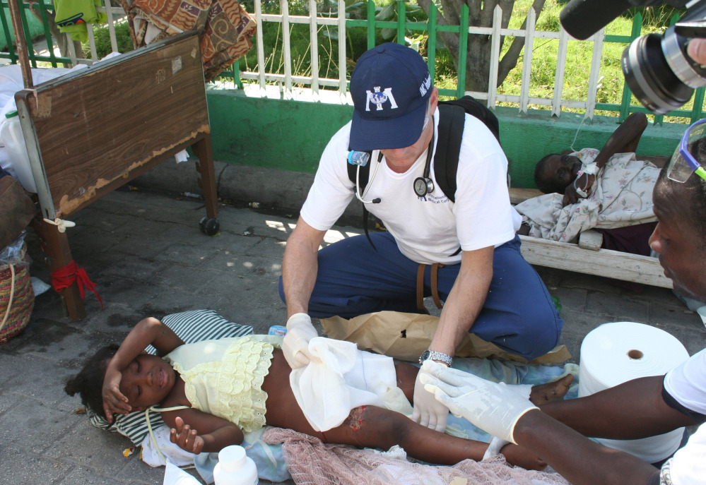 Dr. Robert Fuller provides medical care to an earthquake survivor in Port-au-Prince, Haiti, in 2010. Three weeks of quarantine imposed on medical professionals who volunteer to go to West Africa to help care for Ebola patients adds to the complications of volunteering, and it isn't likely that Fuller will be able to participate.