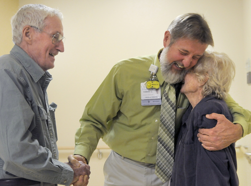 Physical therapist Vinny Lord hugs Anita Smart recently while shaking hands with her husband, Jack, in the rehabilitation facility at MaineGeneral Medical Center. Lord assisted Anita Smart in recovery from a stroke this spring. The Hallowell couple made a sizable donation to the hospital and wanted to thank the therapist for his care, Jack Smart said.