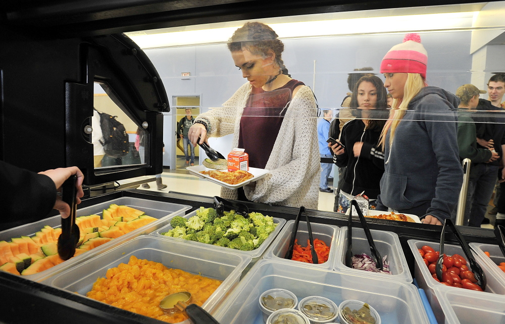 Abby Davis, a junior, adds fruit to her lunch as students at Kennebunk High School are given the opportunity to select vegetarian entrées and fruits and vegetables.