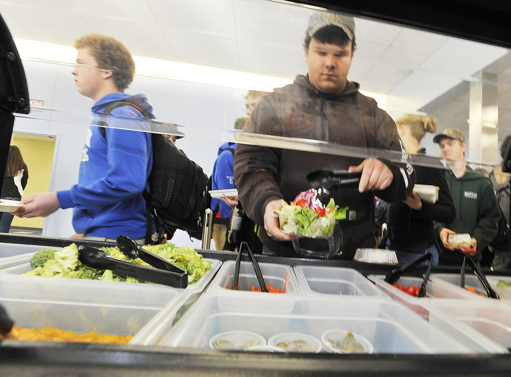 Senior Kenny Davis adds a cherry tomato to his salad Kennebunk High School's cafeteria.