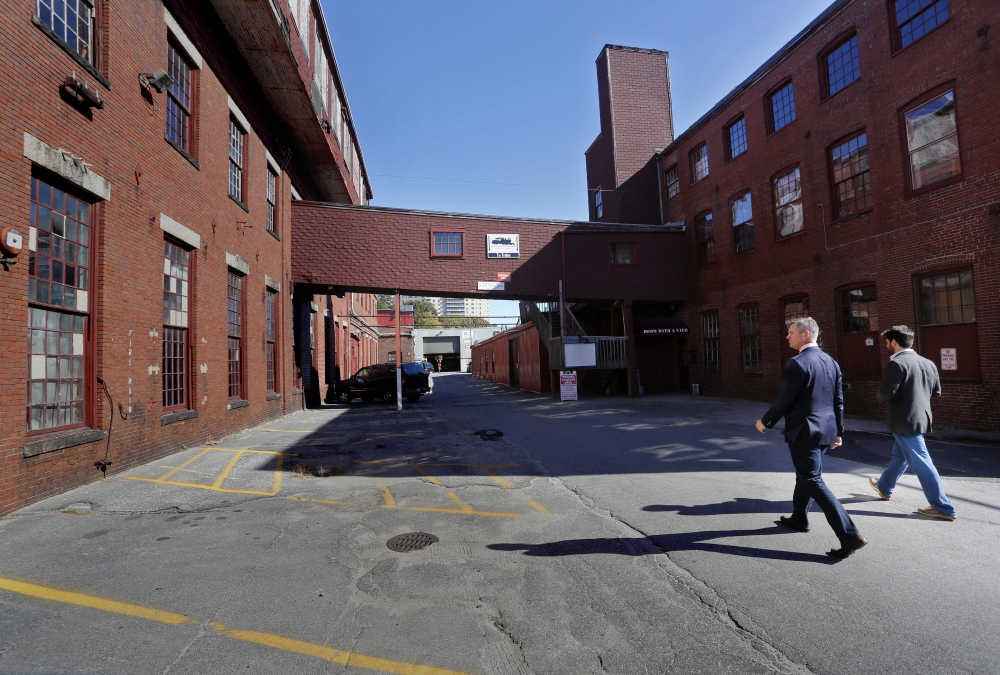 James Brady, left, and Casey Prentice, owners of the former Portland Co. complex, walk around the site in October. A zoning request to the Portland Planning Board asks for the waterfront site to be classified as mixed-use. All that the developers have  promised so far is that none of the proposed buildings will rise higher than 35 feet above Fore Street. Derek Davis/Staff Photographer