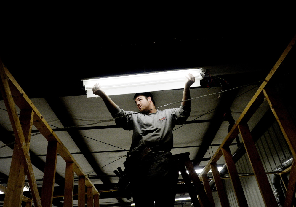 Ryan Lambert of Superior Electrical Contracting installs new lighting at Cuddledown in Yarmouth, in a project aided by a $14,741 grant from Efficiency Maine. The Public Utilities Commission voted in March to restrict funding for energy efficiency programs.