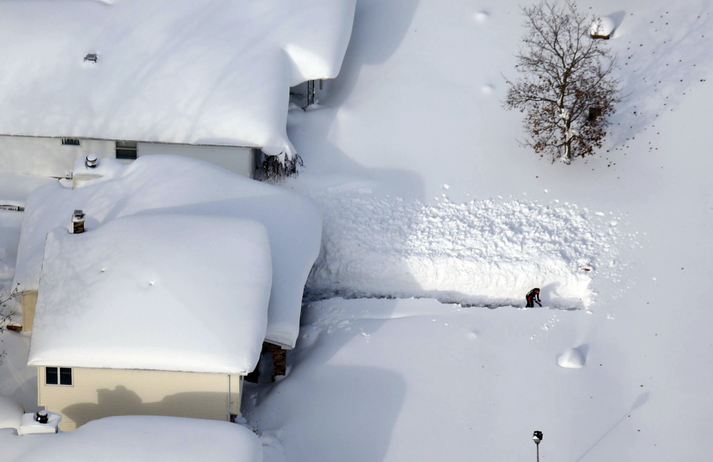 A man digs out his driveway in Depew, N.Y. The worst is expected for the Buffalo area Monday when, with temperatures around 60 degrees, snow will melt faster than it can be absorbed by the ground or snowpack.