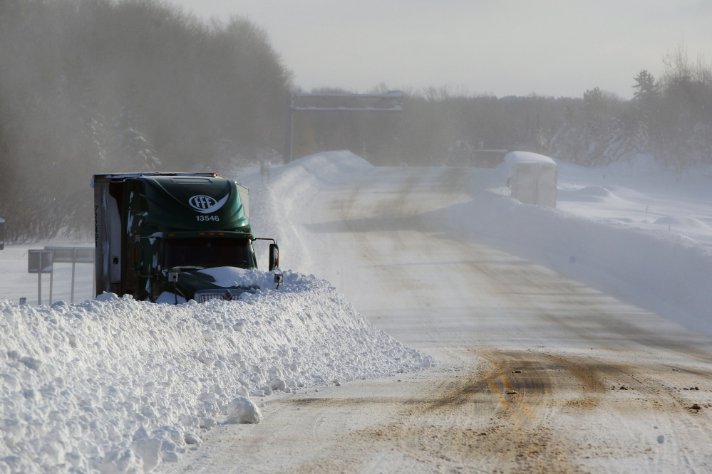Snow covers a stranded truck in Orchard Park, N.Y.