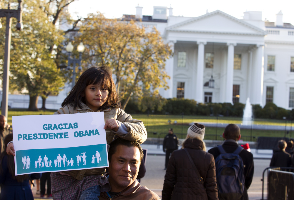 Israel Montalvo holds up his daughter Brianna for a photo while attending a pro-immigration rally in front of the White House on Friday, Nov. 21, 2014. The Associated Press