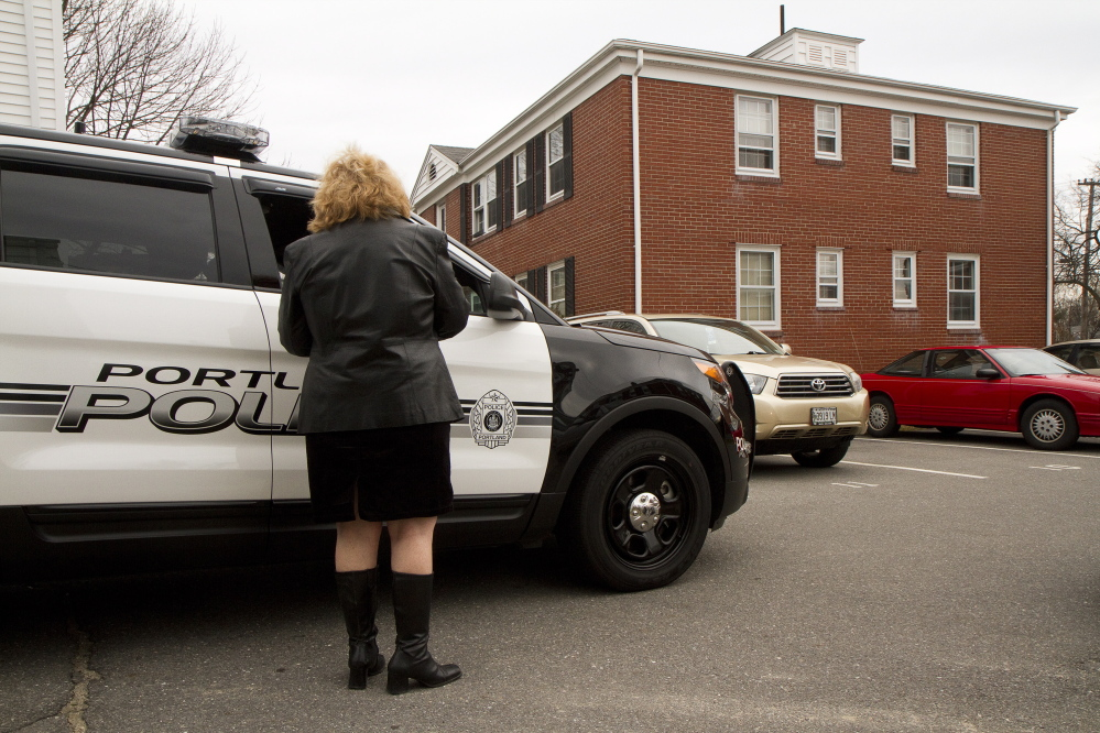Barbara Harvey, who lives near the scene of a fatal shooting at 214 Brighton Ave. in Portland Friday night, talks with a Portland Police officer outside the scene Saturday. Carl D. Walsh/Staff Photographer
