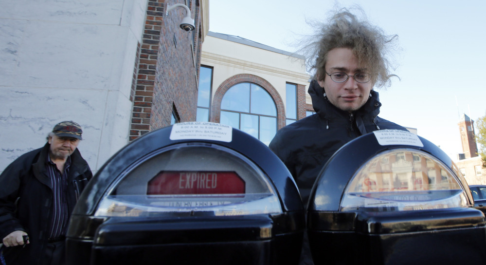 """Garret Ean, a self-proclaimed """"Robin Hooder,"""" puts money in expired meters before a parking enforcement officer in Keene, N.H., can write a ticket. The activists In Keene say they are protesting """"the King's tarrif"""" – or what they see as government oppression."""