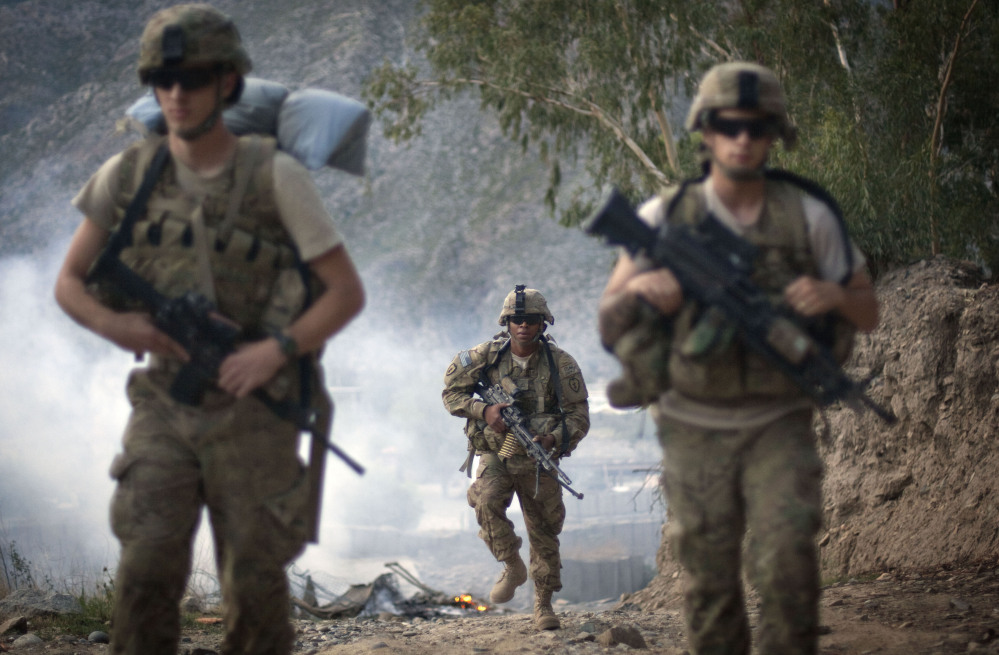 U.S. Army Pfc. Garrick Carlton, center, of Sacramento, Calif., hikes past burning rubbish to man a hilltop observation post along with fellow Pfc. Michael Tompkins, of Wadsworth, Ohio, left, and Pfc. Austin D'Amica, of San Diego, at Combat Outpost Monti in Kunar province, Afghanistan, in 2011. U.S. officials say President Obama has quietly approved guidelines in recent weeks to allow the Pentagon to target Taliban fighters in Afghanistan, broadening previous plans that had limited the military to counterterrorism missions against al-Qaida after 2014.