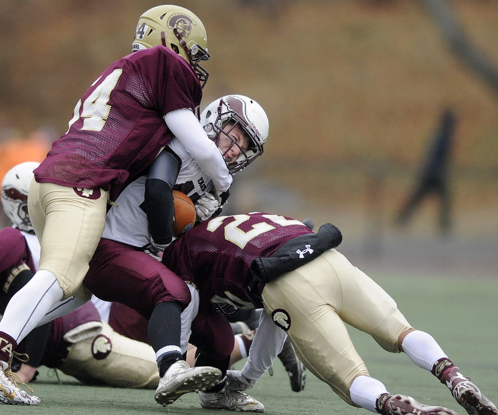 Windham running back Dylan Koza is hauled down by Thornton Academy defenders Dederick Eastup, left, and Nathan Watson during the second half of the Class A final. The Golden Trojans shut out Windham in the second half as they rallied for a 35-14 win, earning their second state championship in three seasons.