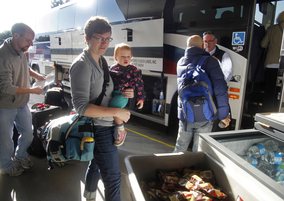 Leah Thibeault of Westbrook her daughter, Autumn, 18 months, and her husband, John, left, are among the throng of holiday travelers this week. The Thibeaults are traveling from Maine to southern California for Thanksgiving.