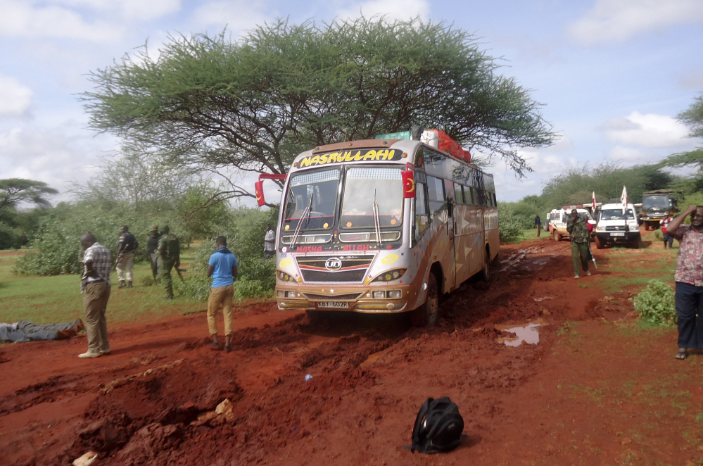 Kenyan security forces and others gather around the scene of an attack on a bus near the Somali border Saturday. Somalia's Islamic extremist rebels, al-Shabab, attacked the bus in Kenya at dawn Saturday, killing 28 passengers.