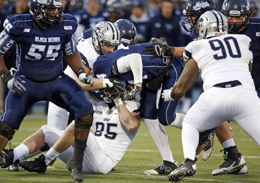 Maine quarterback Drew Belcher (14) gets sacked by New Hampshire's Cody Muller (96) and defensive end Brian Ciccone (85) during the first half Saturday  in Orono.