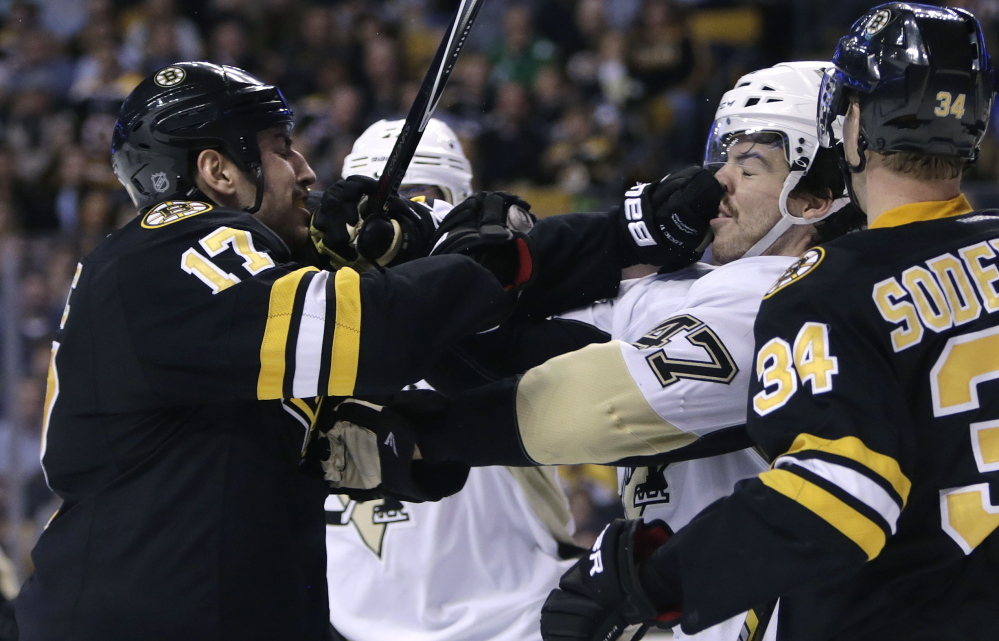 Boston Bruins left wing Milan Lucic jabs Pittsburgh Penguins defenseman Simon Despres in the face during the second period of Monday night's game in Boston.