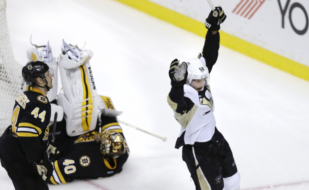 Pittsburgh Penguins defenseman Kris Letang celebrates the game-winning goal by teammate Evgeni Malkin as Boston Bruins goalie Tuukka Rask rolls over at the end of Monday night's game. The Penguins defeated the Bruins, 3-2.