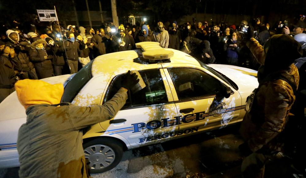 Protesters vandalize a police car outside Ferguson's city hall Tuesday night. It was the second night of unrest in Ferguson, after a grand jury's decision not to indict police officer Darren Wilson in the fatal shooting of Michael Brown.