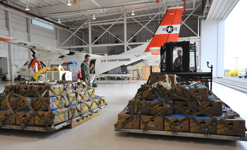 Coast Guardsmen Trey Edenfield, left, directs Henry Rusher as he moves a pallet of of Kemp's Ridley sea turtles at the Coast Guard Air Station Cape Cod Tuesday, Nov. 25, 2014, in Bourne, Mass., to be loaded onto a Coast Guard flight to Orlando, Fla. The stranded turtles, nearly 200 and weighing up to 10 pounds, were collected by the Massachusetts Audubon Society at Wellfleet Bay and were to be sent to marine rehabilitation facilities in Florida. (AP Photo/The Cape Cod Times, Steve Heaslip)  MANDATORY CREDIT; MAGS OUT; NO SALES; TV OUT