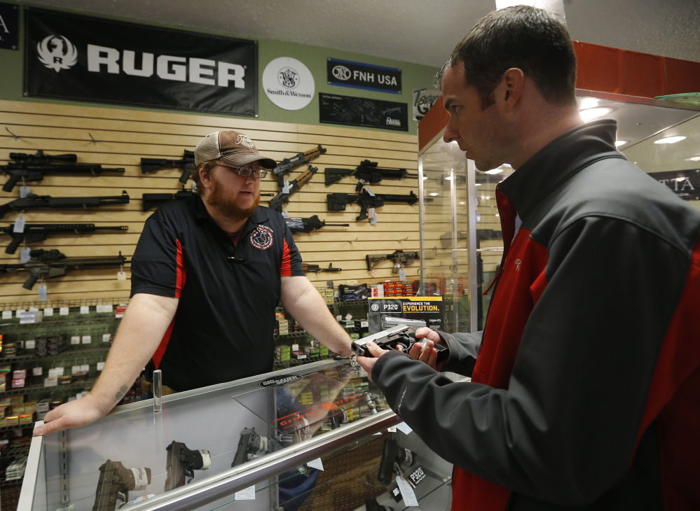 Metro Shooting Supplies employee Chris Cox, left, speaks to customer Steve Christy about the purchase of a 9mm handgun at the shop in Bridgeton, Mo.