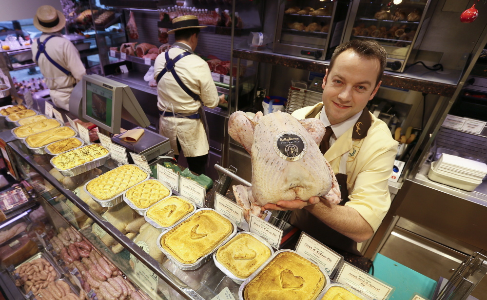 Danny Lidgate displays a turkey Tuesday at his butcher shop inside the high-end Lidgate's store in London. He says Americans gobble up the heritage Kelly Bronze turkeys he stocks.