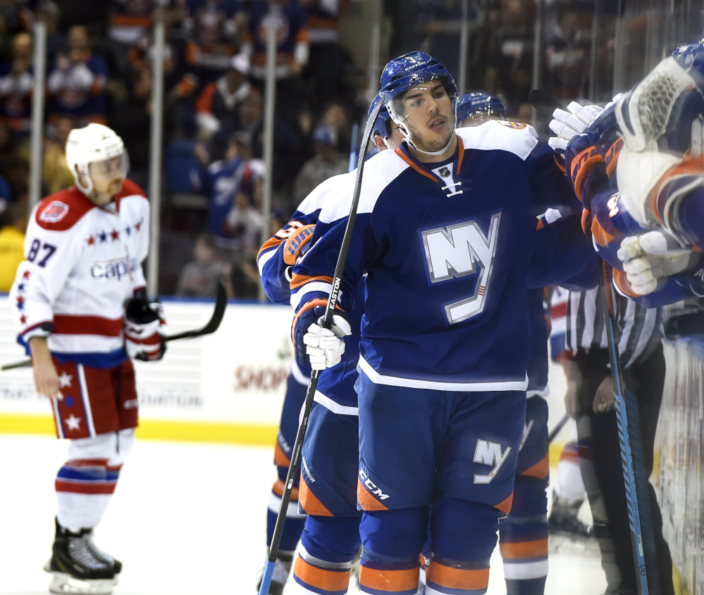 Islanders defenseman Travis Hamonic celebrates his goal as Washington's Liam O'Brien skates to the bench in the first period Wednesday night at Uniondale, N.Y. The Islanders won again, 3-2 in overtime, to set a franchise record by winning 16 of their first 22 games.