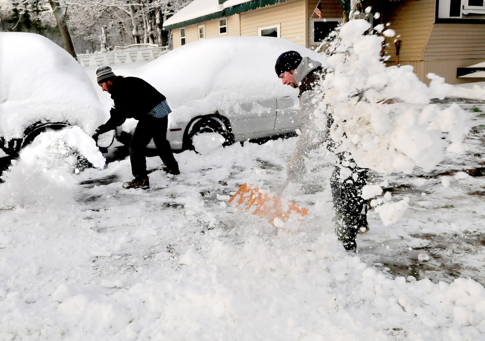 Richard Foster, left, and his brother Rob heave snow in Benton after a storm ended early Thursday morning. Lewiston reported the greatest snowfall – 15 inches – while York County got 12-14 inches and Portland saw 8.5 inches.