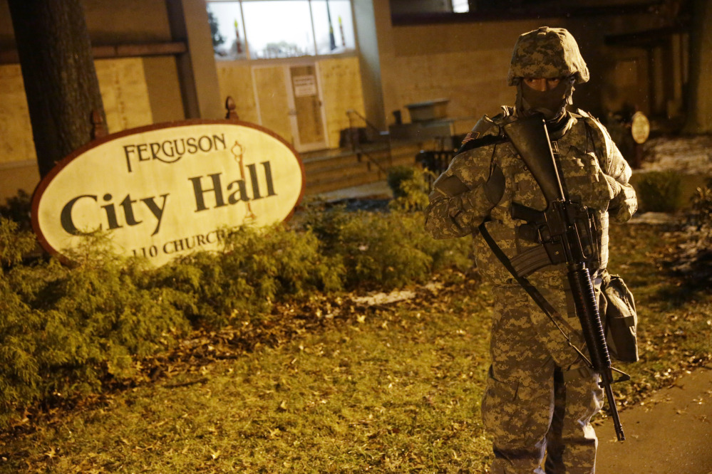 A Missouri National Guardsman stands in front of Ferguson City Hall early Thursday. About 100 people marched in a light snow overnight, but there were no reports of major confrontations or damage to property.