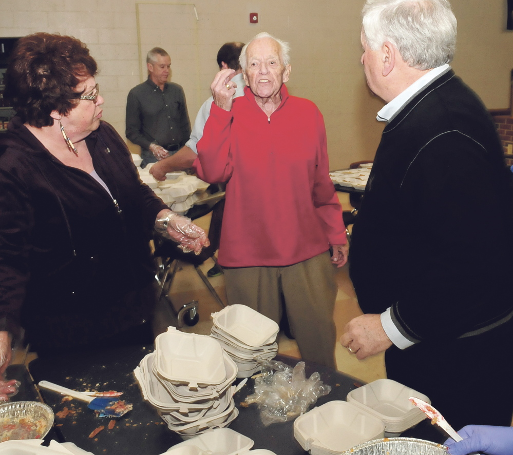 Bud King, center, speaks with volunteers preparing meals Thursday during the annual Thanksgiving dinner at Messalonskee High School in Oakland.