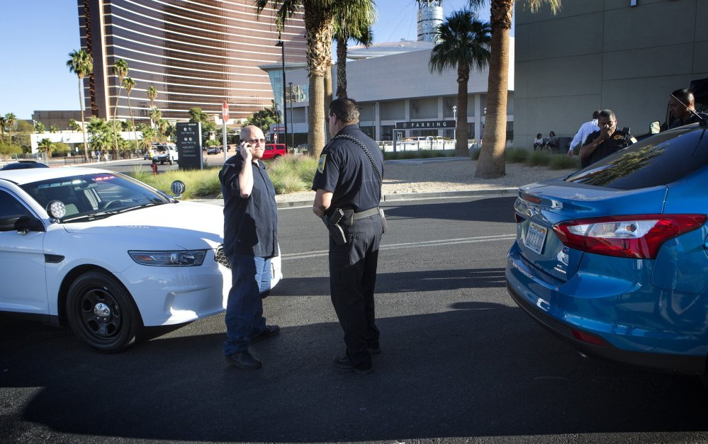 Uber driver Michael Elsner, left, calls an Uber representative after being detained by the Nevada Transportation Authority in front of the Fashion Show mall in Las Vegas last month.