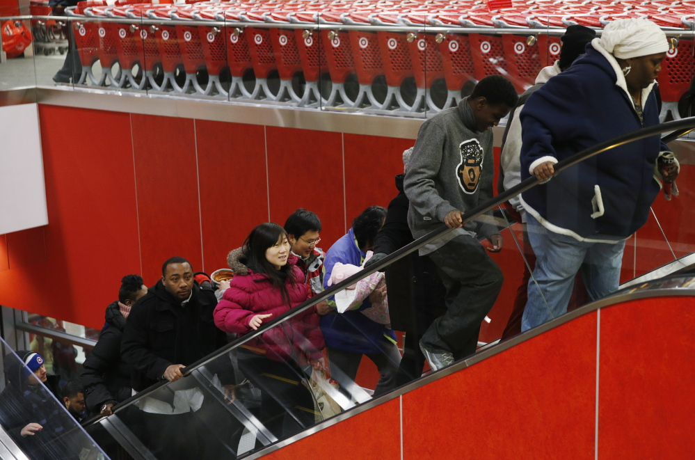 Thanksgiving Day shoppers ride an escalator at a Target store in Chicago. As the lines blur between in-store and digital shopping, retailers say they must win over these shoppers if they are to thrive in a fast-changing retail landscape.