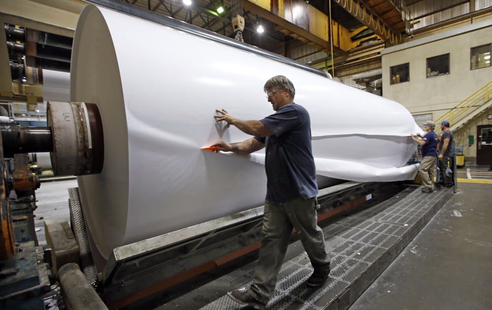 Workers cut a sample section off a large roll of paper made at the Sappi Paper Mill in Skowhegan. The death of Maine's paper industry, once a point of entry to the middle class for thousands, is accelerating as mills close, lose value, and declare bankruptcy. A mill in Bucksport recently announced it will close and a mill in Millinocket declared bankruptcy.