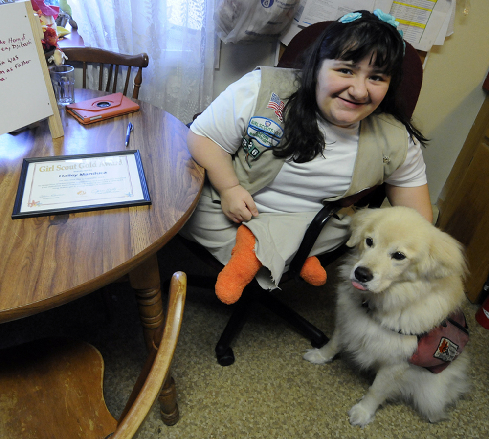 Hailey Manduca, 16, sits with her service dog at home in Bourne, Mass. Born with brittle bone disease, she excels in Girl Scouts and has earned its top honor: the Gold Award.
