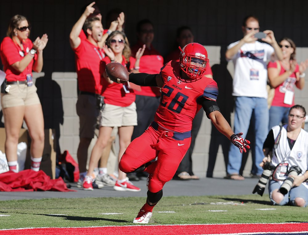Arizona safety Anthony Lopez celebrates after recovering a fumble for a touchdown during the first half of Friday's game against Arizona State in Tucson, Ariz.