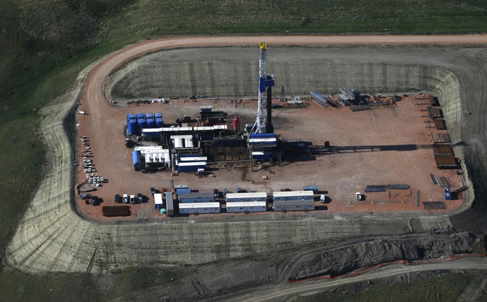 Oil is drilled near Williston, N.D., in June. A decision by the Organization of Petroleum Exporting Countries not to cut oil production is hammering major energy companies in the U.S. and abroad. Shares of companies across the energy industry fell. Chevron Corp. slid 5 percent while Exxon Mobil fell 4 percent.