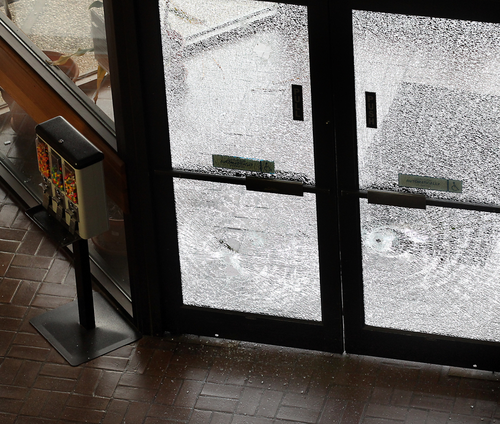 Doors filled with broken glass are photographed after authorities shot and killed a man who they say opened fire on the Mexican Consulate, police headquarters and other downtown buildings early Friday in Austin, Texas.