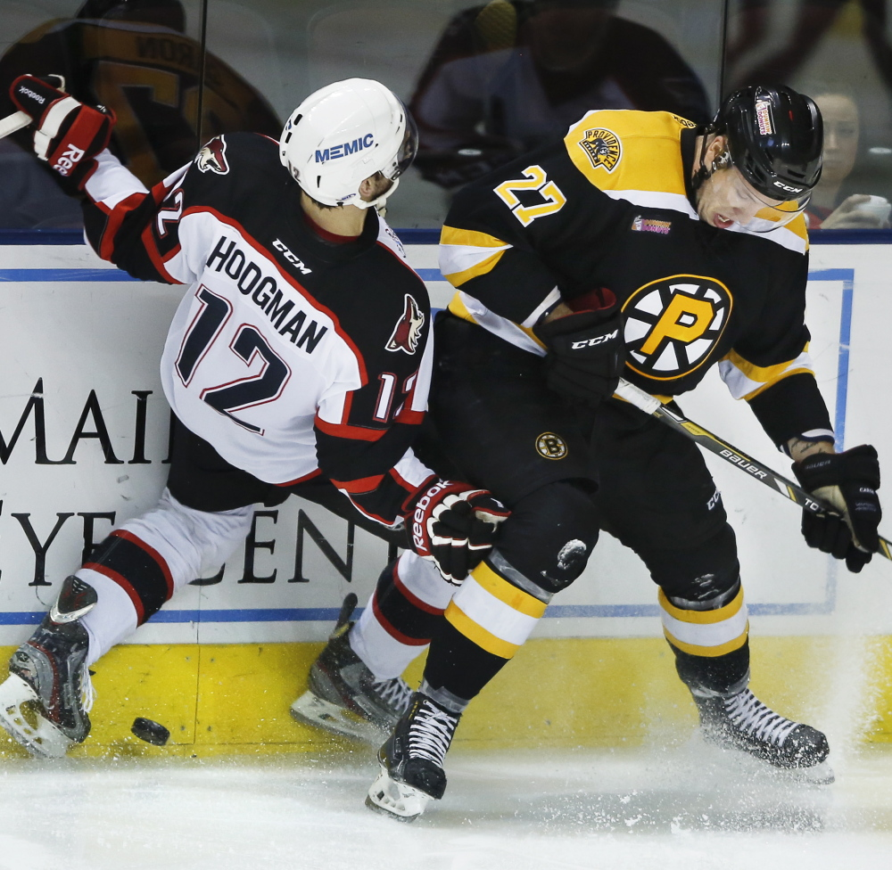 Justin Hodgman of the Portland Pirates, left, starts a spill to the ice while competing for the puck along the boards with Jordan Caron of the Providence Bruins.