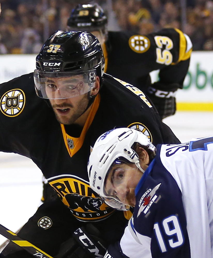 Boston's Patrice Bergeron and Winnipeg's Jim Slater are all eyes as they battle for a loose puck during the second period of the Bruins' come-from-behind victory at home.