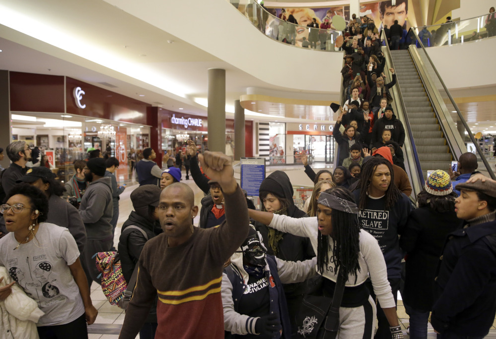 The Associated Press Protesters march inside Chesterfield Mall Friday in Chesterfield, Mo. The crowd disrupted holiday shopping at several locations on Friday amid a protest triggered by a grand jury's decision not to indict the police officer who fatally shot Michael Brown in nearby Ferguson.