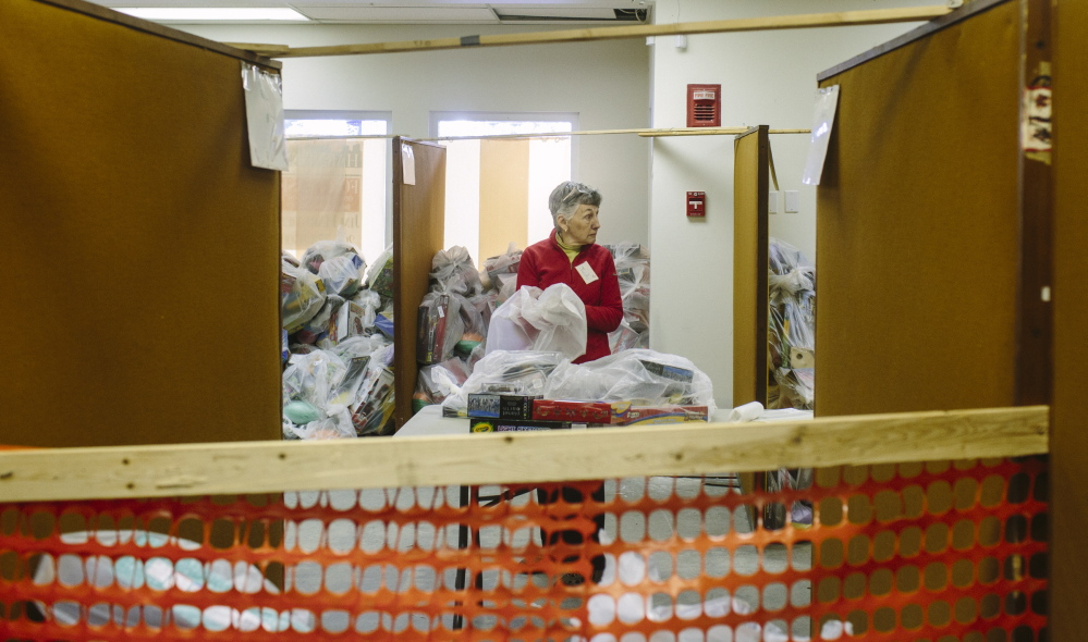 Judy Oliver packs toys for the Portland Press Herald Toy Fund in Freeport. The charity hopes to raise $250,000 this year.