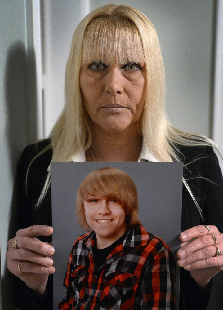 """Donna Pitcher holds a photo of her 18-year-old son, Dylan Collins, which was taken this year. She said she tried all summer to have him committed to a psychiatric facility. """"I did everything I could to sound the alarm,"""" she said."""