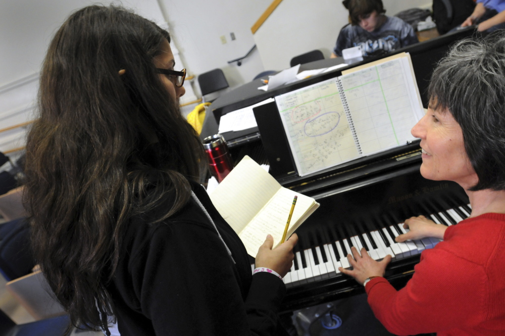 In this Nov. 19, 2014 photo, Northampton High School freshman Lexi Matuson, left, works out the right chords for her original composition with choral director Beau Flahive during a songwriting class held in the school's Little Theater in Northampton Mass. The school's new songwriting course this year gives students the opportunity to write and perform original music. (AP Photo/Daily Hampshire Gazette, Kevin Gutting)