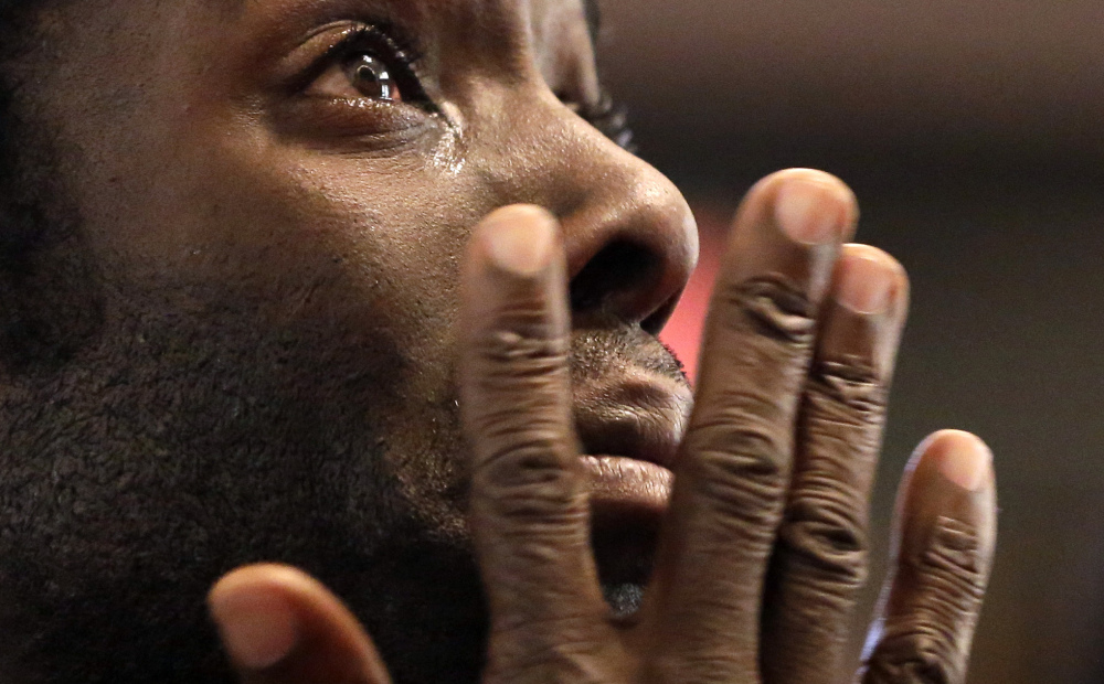 Desmond Cole wipes away tears as he takes part in a prayer service Saturday in St. Louis before starting off on a 120-mile march to the governor's mansion in Jefferson City. After the service, the marchers traveled by bus to Canfield Drive in Ferguson, where Michael Brown was killed, to start the seven-day walk organized by the NAACP.