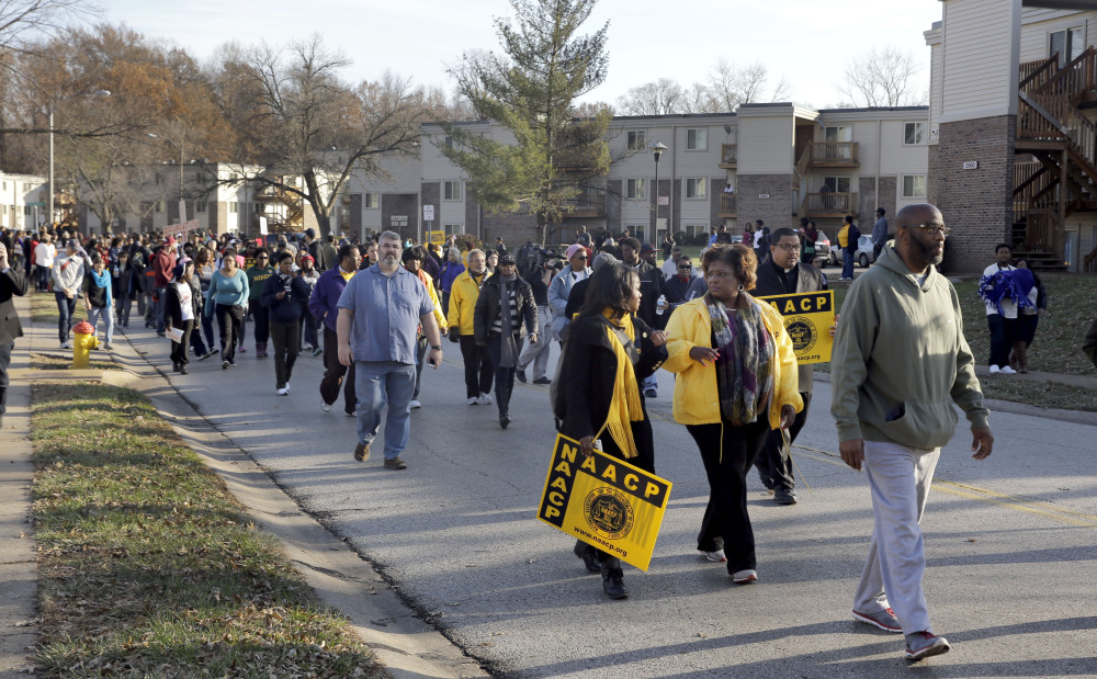 Hundreds march away from the area where Michael Brown was killed Saturday, Nov. 29, 2014, in Ferguson, Mo., at the start of a 120-mile march to the governor's mansion in Jefferson City. The march, organized by the NAACP to evoke civil rights marches from the 1960s, began Saturday afternoon on Canfield Drive in Ferguson where Michael Brown was killed and is expected to last seven days. (AP Photo/Jeff Roberson)