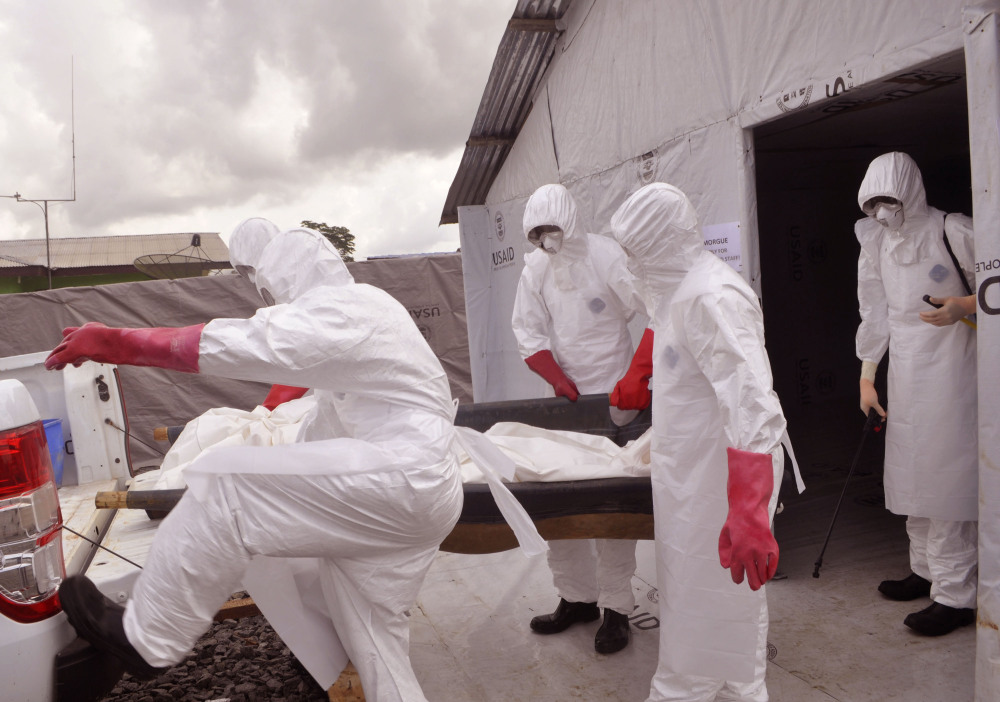 Health workers wearing Ebola protective gear remove the body of a man they suspect died from the Ebola virus, at a USAID, American aid Ebola treatment center at Tubmanburg on the outskirts of  Monrovia, Liberia.