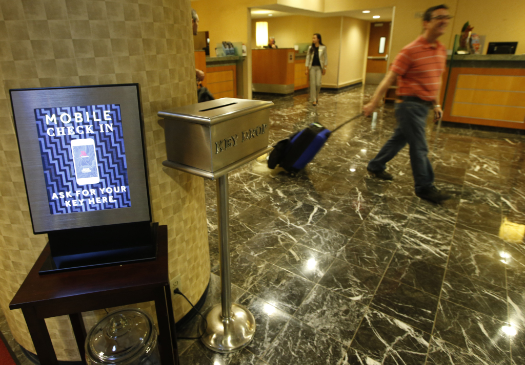In this Oct. 14, 2014, photo, hotel guest J.D. Solomon, of Indianapolis, right, strolls out of the lobby after using the mobile check-in counter at the Marriott Marquis Times Square hotel in New York. Marriott International launched the ability to check in through its app at 330 North American hotels last year. By the end of this year, the program will be live at all 4,000 hotels worldwide. The Associated Press