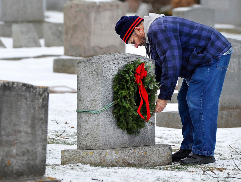 In this Dec. 8, 2014, Charlie Davis of Old Orchard Beach replaces the wreath that was stolen from the headstone of the grave of his parents and grandparents in Laurel Hill Cemetery in Saco.