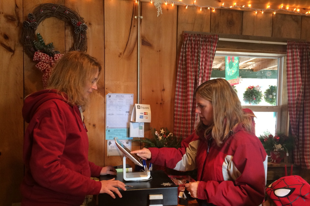 Kimberly Solberg, right, of Madison, pays Melissa Fredsall for a Christmas tree at Trees to Please on Sunday. The tree farm has lost about five percent of their profit this year from people stealing trees and wreaths, says owner Todd Murphy. Staff photo by Rachel Ohm