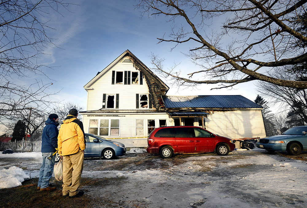 David Buck looks over his fire-damaged home at 1573 Goodwins Mills Road in Waterboro along with his son Brian Buck, left, on Monday. Shawn Patrick Ouellette / Staff Photographer