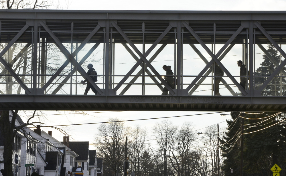 Students cross the USM Alumni Skywalk on the campus in Portland on Monday. Faculty members and students have decried the cuts at the university, saying they go too far.