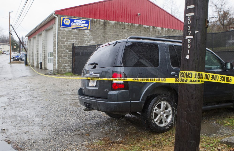 Police vehicles are parked outside Doug's Towing in Westover, W.Va., on Monday, after three separate shootings left four people dead.