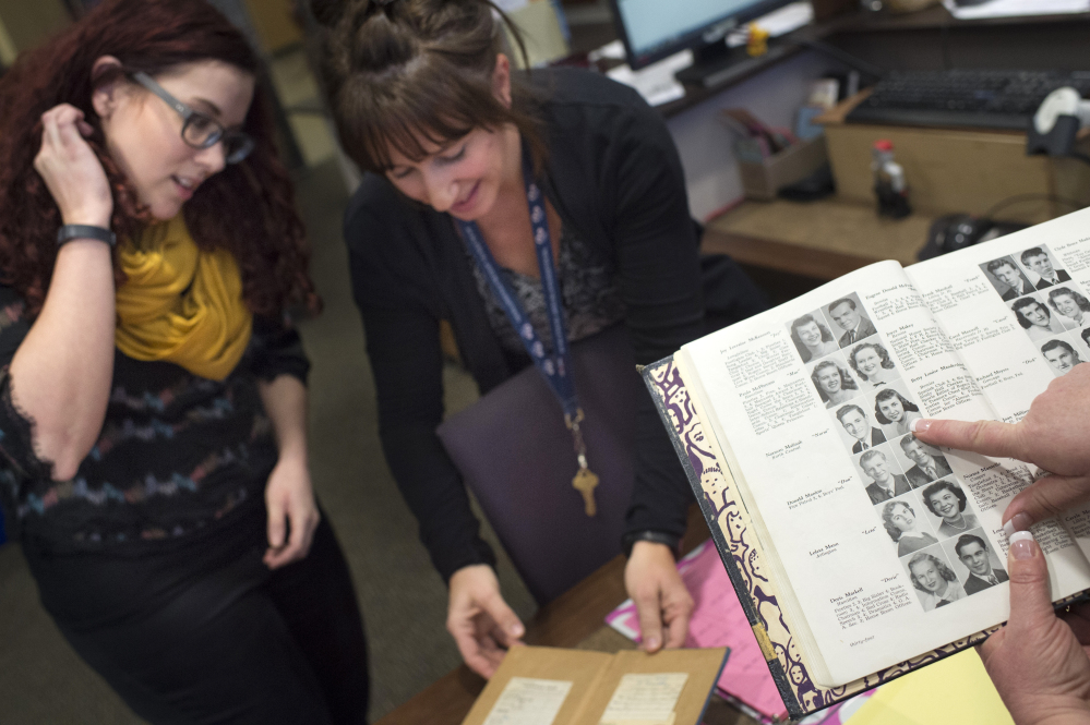 """Rogers High School librarian Becky Huss, left, checks out a long-overdue copy of """"Gone With The Wind,"""" with school literacy coach Tracy Schumacher, center, as school Principal Lori Wyborney finds a photo of the last student to check out the book in a 1949 yearbook in Spokane, Wash."""
